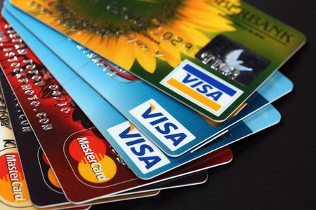 Tambov, Rusland - 11 september 2012 Hoop van credit cards van Visa en Mastercard logo's op zwarte achtergrond. Studio-opname. Visa en Mastercard zijn twee grootste creditcardmaatschappijen ter wereld.