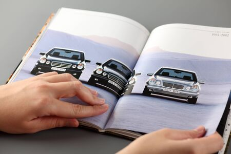 browses: Tambov, Russian Federation - November 3, 2012 Woman browses a catalog at a Mercedes-Benz cars dealership. She opens pages with three cars, which produced in 1995-2002. Studio shot. Mercedes-Benz brand is used for luxury automobiles, buses, coaches, and tr Editorial