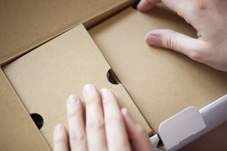 unpacking: Womans hands unpacking cardboard box. Focus on the box. Stock Photo
