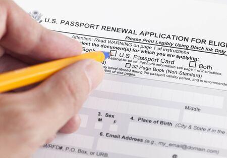 eligible: US domanda di rinnovo del passaporto per gli individui ammissibili e mano umana con penna a sfera.