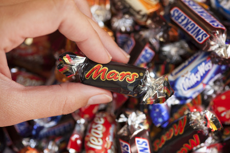 mars incorporated: Paphos, Cyprus - December 19, 2013 Mars candy in womans hand with background of Snickers, Mars, Twix, Milky Way, Galaxy, Bounty and Maltesers Teasers candies. Studio shot. All these candies manufactured by Mars, Incorporated. Editorial