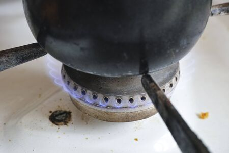 gas cooker: Pot on flame burning of old dirty gas cooker .