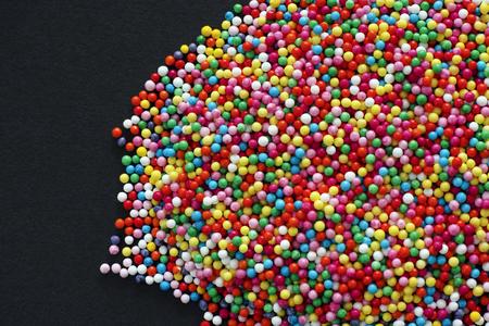 Multicolor sprinkles on black background