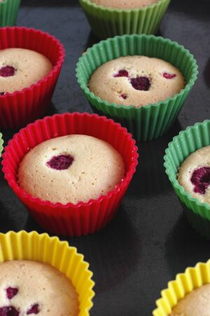 sponge cake: Freshly baked sponge cake muffins with raspberry and without icing.