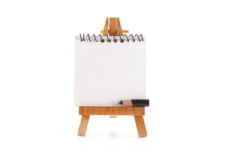 billboard posting: Wooden easel with pencil and spiral notebook isolated on white background