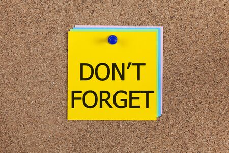 billboard posting: Paper notes with words Dont forget on corkboard (bulletin board).