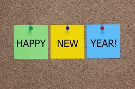 billboard posting: Three blanks Paper notes on corkboard (bulletin board) with words �Happy New Year!�.