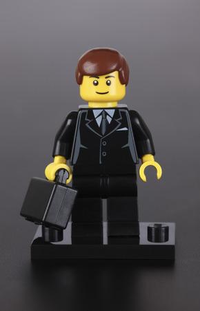 Tambov, Rusland - 4 oktober 2013 Lego zakenman figuur met zwarte koffer op een zwarte achtergrond. Studio-opname. LEGO is een populaire lijn van constructiespeelgoed vervaardigd door de Lego Group (Billund, Denemarken).
