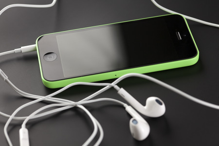 handsfree device: Tambov, Russian Federation - October 16, 2013: Apple iPhone 5C Green Color, Apple EarPods on black background. Studio shot. Apple iPhone 5C Green Color, Apple EarPods on black background. iPhone 5C is produced by Apple Computer, Inc.