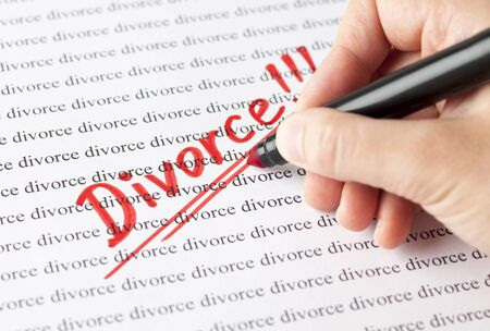 Womans hand with red pen writing word Divorce !!! on the background of words divorce. Stock Photo