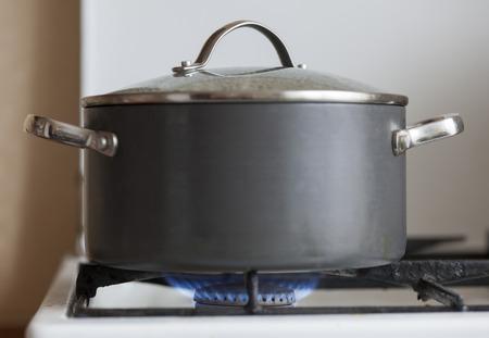 gas cooker: Olla con tapa en la quema de llama de la cocina de gas de edad Foto de archivo