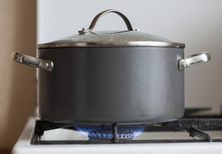 gas cooker: Pot with cover on flame burning of old gas cooker