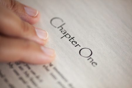 chapter: Womans hand on book page with title Chapter One. Shallow depth of field.