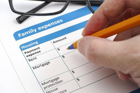 questionary: Family expenses applicacion form, glasses and human hand with ballpoint pen. Stock Photo