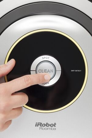 carpet clean: Tambov, Russian Federation - January 26, 2014 iRobot Roomba 630 Vacuum Cleaning Robot. Womans finger pressing the button Clean to starting cleaning. Studio shot.