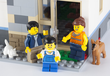 Tambov, Russian Federation - January 08, 2014 Happy LEGO family standing near his home with pets. There are minifigures of mom, dad, son, cat and dog. Studio shot. Lego manufactured by the Lego Group (Billund, Denmark). Editorial