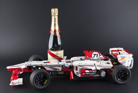 technic: Tambov, Russian Federation - January 12, 2014: LEGO Technic Grand Prix Racer model with bottle of Champagne G.H.Mumm Brut Cordon Rouge on black background. Item 42000. It model motorized with 8293 LEGO Power Functions Motor Set. Studio shot. G.H. Mumm is