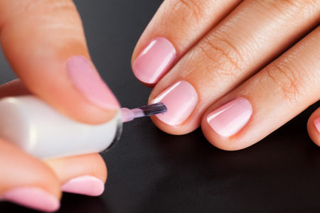 pink nail polish: Painting nails. Black background. Stock Photo