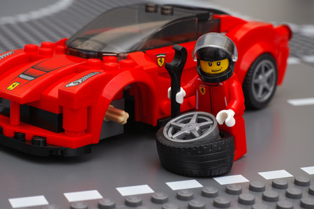 Tambov, Russian Federation - March 05, 2015 Lego driver minifigure is fixing wheel of LaFerrari by LEGO Speed Champions on the Lego road baseplates. Studio shot.