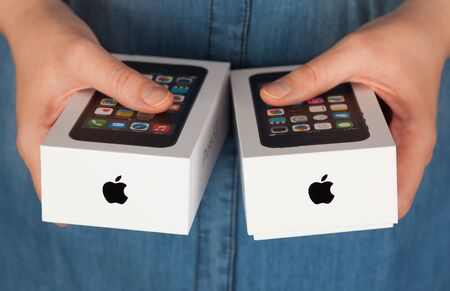 mobilephone: Tambov, Russian Federation - January 12, 2015 Two Apple iPhone boxes in womans hands.  Studio shot. Editorial