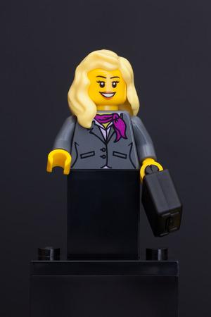 Tambov, Russian Federation - June 08, 2015 Lego businesswoman minifigure with black suitcase on black background. Studio shot.