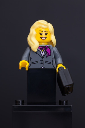 Tambov, Russian Federation - June 08, 2015 Lego businesswoman minifigure with black suitcase on black background. Studio shot.