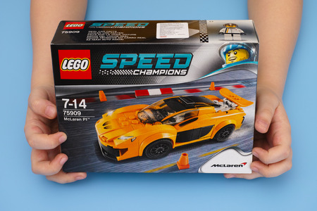 yellow lego block: Tambov, Russian Federation - March 04, 2015 LEGO Speed Champions box with McLaren P1 in childs hands. Studio shot. Editorial