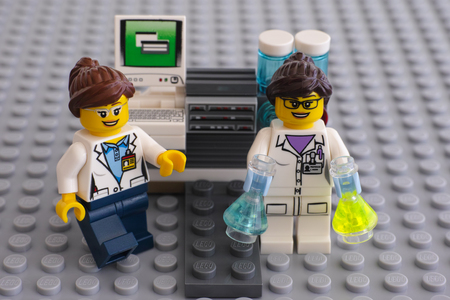 Tambov, Russian Federation - June 10, 2015 Two LEGO scientists minifigures near laboratory computer on Lego gray baseplate.