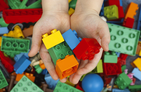 Tambov, Russian Federation - February 20, 2015 Lego Duplo Bricks in childs hands with Lego Duplo blocks background. Studio shot. Lego Duplo is a toys for children age 1,5-5 (manufactured by the Lego Group (Billund, Denmark)).