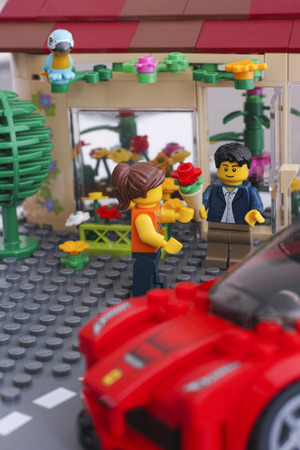 custom car: Tambov, Russian Federation - March 11, 2015 Lego man minifigure with bouquet and Lego girl near flowers shop. Lego Ferrari car on the front. Custom set. Studio shot. Editorial