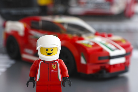 Tambov, Russian Federation - March 18, 2015 Lego Ferrari driver minifigure by LEGO Speed Champions and his car Ferrari 458 Italia GT2 on background. Studio shot.