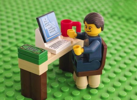 Tambov, Rusland - 24 maart 2015 Lego zakenman zit aan zijn werktafel met computer, geld en kop op Lego groene basisplaat achtergrond. Studio-opname.