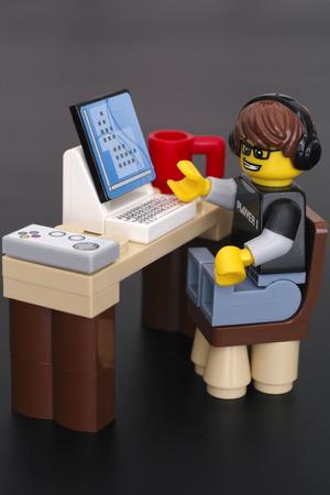 Tambov, Rusland - 24 maart 2015 Lego Video Game Guy minifigure (speler 1) aan zijn tafel met een computer, gamepad en kop op zwarte achtergrond. Studio-opname. Redactioneel