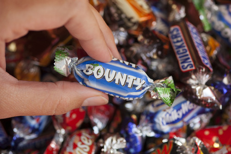 Paphos, Cyprus - December 19, 2013 Womans hand holding Bounty candy against background of candies manufactured by Mars, Incorporated. Studio shot. Bounty candy in womans hand with background of Snickers, Mars, Twix, Milky Way, Galaxy, Bounty and Maltese