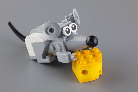 creator: Tambov, Russian Federation - March 20, 2014 LEGO mouse with cheese on grey background. It is LEGO Creator Furry Creatures set. Studio shot. LEGO is a popular line of construction toys manufactured by the Lego Group (Billund, Denmark).