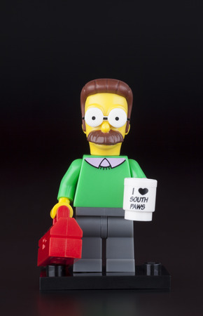 neighbor: Tambov, Russian Federation - April 30, 2014 LEGO Ned Flanders minifigure with mug and red suitcase on black background. Studio shot. Ned Flanders is the next door neighbor to the Simpson family and is generally loathed by Homer Simpson.