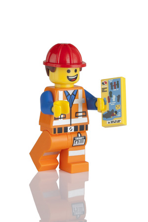 Tambov, Russian Federation - May 16, 2014 LEGO Hard Hat Emmet minifigure with instructions booklet on white background. LEGO Movie series. Studio shot. LEGO is a popular line of construction toys manufactured by the Lego Group (Billund, Denmark).