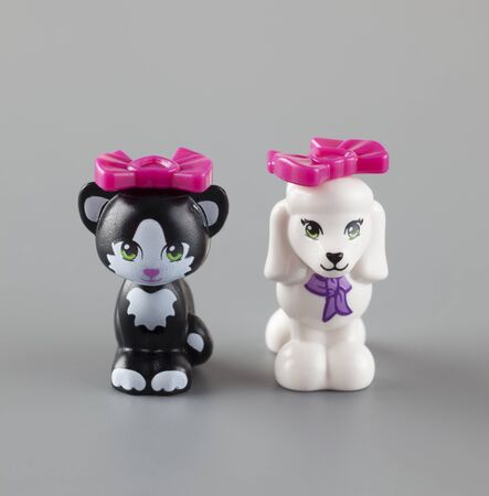 product range: Tambov, Russian Federation - September 11, 2013 LEGO Friends Poodle and Cat minifigures with pink bows on grey background. Studio shot. Lego Friends is a product range of the Lego construction toy designed to appeal primarily to girls.