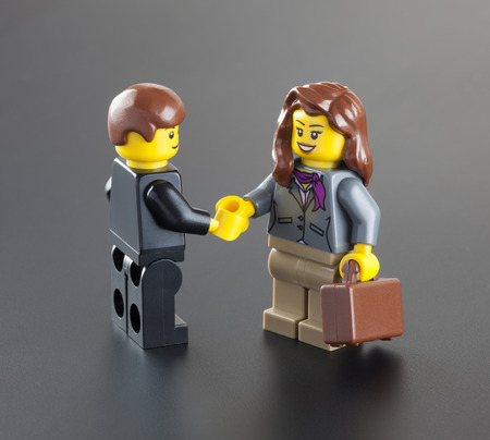 Tambov, Russian Federation - October 04, 2013 Lego minifigures businessman and businesswoman with suitcase shaking hands on black background. Studio shot. LEGO is a popular line of construction toys manufactured by the Lego Group (Billund, Denmark).