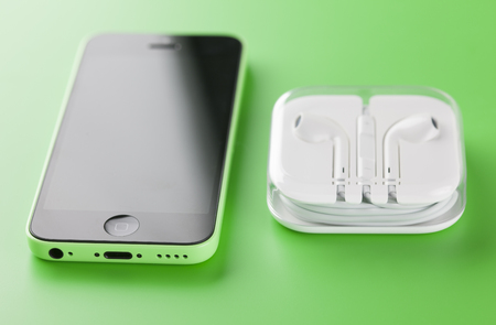 handsfree device: Tambov, Russian Federation - October 16, 2013 Apple iPhone 5C Green Color with new Apple EarPods in plastic box on green background. Studio shot. iPhone 5C is produced by Apple Computer, Inc.