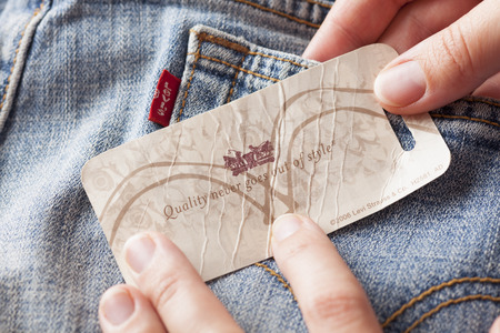 levi: Tambov, Russian Federation - October 21, 2012 Womans hand taking label logo with phrase «Quality never goes out of style» on the pair Levis Jeans. Studio shot. Levi Strauss & Co. is a American clothing company was founded in 1853. It known worldwide f