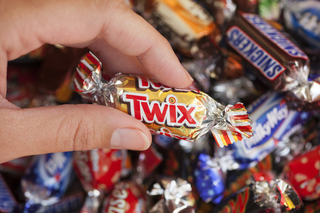 mars incorporated: Paphos, Cyprus - December 19, 2013 Twix candy in womans hand with background of Snickers, Mars, Twix, Milky Way, Galaxy, Bounty and Maltesers Teasers candies. Studio shot. All these candies manufactured by Mars, Incorporated. Editorial