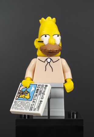simpson: Tambov, Russian Federation - February 07, 2015 Lego Abraham Jay-Jedediah Abe Simpson minifigure with newspaper on black background. Studio shot. Editorial