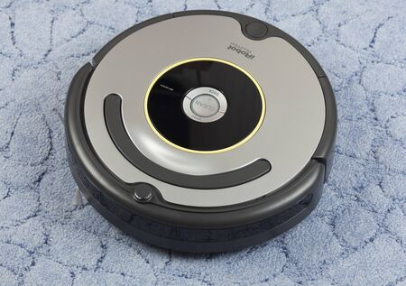 vac: Tambov, Russian Federation - January 26, 2014 iRobot Roomba 630 Vacuum Cleaning Robot on blue carpet. Studio shot. A robotic vacuum cleaner, often called a robovac, is an autonomous robotic vacuum cleaner that has intelligent programming and a limited vac Editorial