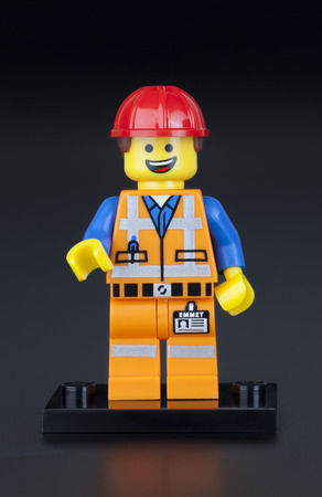 Tambov, Russian Federation - February 10, 2014 LEGO Hard Hat Emmet minifigure on black background. LEGO Movie series. Studio shot. LEGO is a popular line of construction toys manufactured by the Lego Group (Billund, Denmark).