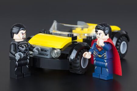 gro: Tambov, Russian Federation - January 11, 2014 Lego minifigures of Superman and General Zod near yellow car on black background. Studio shot. Item 76002. Superman Metropolis Showdown. LEGO is a popular line of construction toys manufactured by the Lego Gro