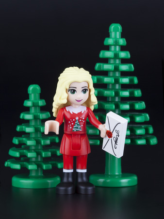 plastic christmas tree: Tambov, Russian Federation - February 10, 2014 LEGO friends girl minifigure in red christmas costume with letter to Santa Claus. There are two Christmas tree behind girl on black background. Studio shot.