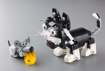 creator: Tambov, Russian Federation - March 18, 2014 LEGO cat and mouse with cheese on grey background.  It is LEGO Creator Furry Creatures set. Studio shot. Item 31021. This cute cat has a playful eye on a mouse friend who is nibbling a piece of cheese. LEGO is a Editorial