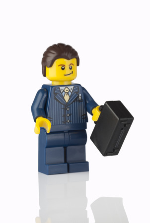 Tambov, Russian Federation - June 21, 2014 Lego businessman minifigure in blue suit with black suitcase on white background. Studio shot. LEGO is a popular line of construction toys manufactured by the Lego Group (Billund, Denmark). Editorial