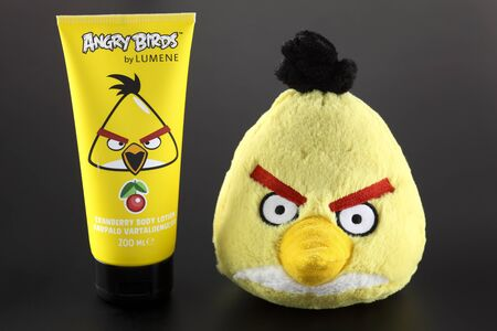 body lotion: Tambov, Russian Federation - September 22, 2013 Yellow Angry Birds soft toy and Angry Birds by LUMENE Cranberry Body Lotion on black background. Studio shot. Angry Birds is popular computer games, developed by Rovio Mobile. Lumene is a Finnish brand of co